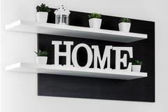 La maison marque avec des lettres le décor sur l'étagère blanche photographie stock