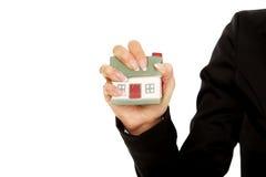 La maison modèle est écrasée dans la main de femme Photographie stock libre de droits