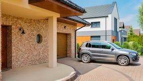 La maison résidentielle avec la voiture argentée de suv a garé sur l'allée dans le fron images libres de droits