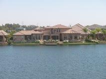 La maison rose de stuc avec le toit de tuile rose enjambe le bord du lac Photographie stock libre de droits