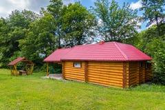La maison se compose d'un cadre en bois avec de petites fenêtres et un toit rouge situé près du belvédère Photo libre de droits
