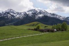 La maison sur la neige a couvert des montagnes avec les collines vertes Images stock