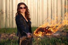 La mala mujer en gafas de sol y una chaqueta negra que sostiene una antorcha al aire libre Foto de archivo libre de regalías