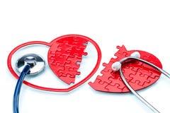 La maladie cardiaque, a dédoublé le puzzle en forme de coeur avec le stéthoscope Photographie stock