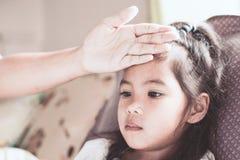 La maladie de fille d'enfant et la main asiatiques mignonnes de mère touchent son front Images libres de droits