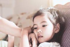 La maladie de fille d'enfant et la main asiatiques mignonnes de mère touchent son visage Image libre de droits
