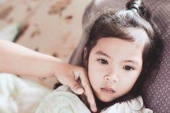 La maladie de fille d'enfant et la main asiatiques mignonnes de mère touchent son visage Photo stock