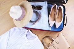 La maleta abierta con la mujer casual viste el sombrero, gafas de sol, camisa blanca, zapatos, bolso en cierre de madera de la op Imagen de archivo