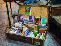 La maleta antigua sirve como espacio de exhibición de libro en outsid de la acera imagen de archivo