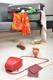 La maleta de la materia y del viaje de la ropa dispersó en sofá Foto de archivo