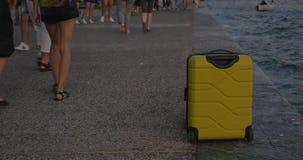 La maleta en las ruedas se coloca en costa de mar en la ciudad de Salónica, Grecia almacen de metraje de vídeo