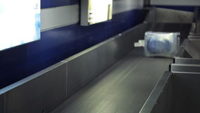 La maleta grande se mueve lentamente en la banda transportadora negra en aeropuerto almacen de video