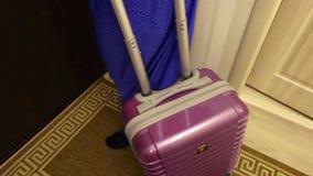 La maleta roja sale del cuarto, el concepto de turismo, salida, tarifas para el viaje almacen de metraje de vídeo