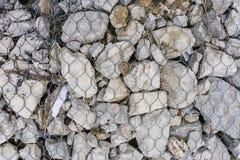 La malla de acero con la piedra gris Imagen de archivo