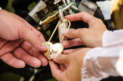 La malla de novia y del novio ralla la cerradura del oro en el puente Foto de archivo libre de regalías