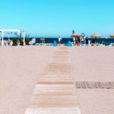 La Malvarrosa Beach in Valencia, Spain. Wooden boardwalk at La Malvarrosa Beach in Valencia, Spain, with the Mediterranean sea and unrecognizable sunbathers in Royalty Free Stock Photo