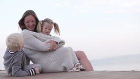 La mamá abraza a los niños para un paseo almacen de metraje de vídeo