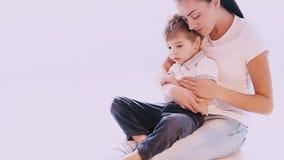 La mamá abraza a su hijo con amor y el afecto almacen de metraje de vídeo