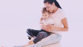 La mamá abraza a su hijo con amor y el afecto almacen de video