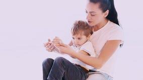 La mamá abraza a su hijo con amor y el afecto metrajes