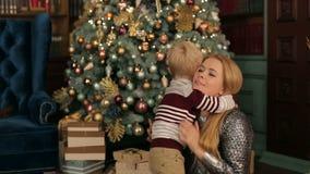 La mamá abraza suavemente a su pequeño hijo cerca del árbol de navidad metrajes