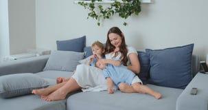 La mamá abraza a sus dos pocos hijos en el sofá en la sala de estar y ve la TV Familia que ve la TV almacen de video