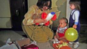 1973: La mamá abre el regalo de la Navidad del coche de carreras del muchacho almacen de video