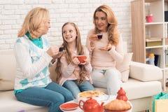 La mamá, la abuela y la niña están bebiendo el té junto, sentándose en la tabla fotografía de archivo
