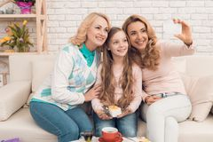 La mamá, la abuela y la niña hacen el selfie que se sienta en el sofá fotos de archivo libres de regalías