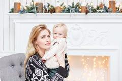 La mamá alegre abraza a su hija linda del bebé Padre y pequeño niño que se divierten cerca del árbol de navidad dentro loving imagen de archivo libre de regalías