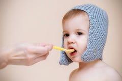 La mamá alimenta al bebé con puré de la fruta Imágenes de archivo libres de regalías