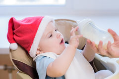 La mamá alimenta al bebé cuyo sombrero del Año Nuevo Imagenes de archivo