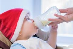 La mamá alimenta al bebé cuyo sombrero del Año Nuevo Fotografía de archivo libre de regalías