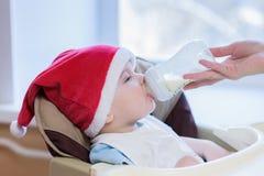 La mamá alimenta al bebé cuyo sombrero del Año Nuevo Imágenes de archivo libres de regalías