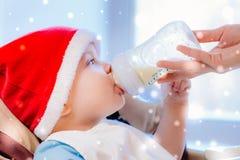 La mamá alimenta al bebé cuyo sombrero del Año Nuevo Fotografía de archivo
