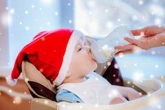La mamá alimenta al bebé cuyo sombrero del Año Nuevo Imagen de archivo