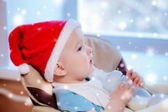 La mamá alimenta al bebé cuyo sombrero del Año Nuevo Foto de archivo libre de regalías