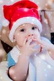 La mamá alimenta al bebé cuyo sombrero del Año Nuevo Foto de archivo