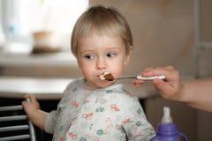 La mamá alimenta al bebé de una cuchara fotos de archivo libres de regalías
