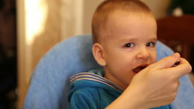 La mamá alimenta las gachas de avena del bebé de una cuchara almacen de metraje de vídeo