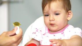 La mamá alimenta a un pequeño niño con una cucharada de verduras El niño no hace como verduras