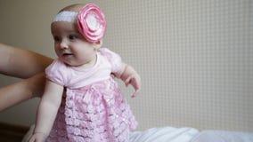 La mamá aprende caminar un pequeño bebé en un vestido rosado almacen de metraje de vídeo