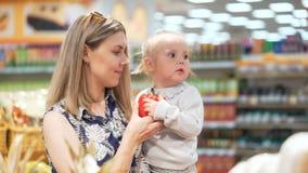 La mamá atractiva con el niño del niño coge la verdura del primer del estante metrajes