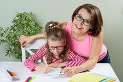 La mamá ayuda al niño a escribir Muchacha 6, 7 años con los vidrios que se sientan en la tabla y que escriben en cuaderno fotografía de archivo