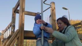 La mamá ayuda al pequeño niño a resbalar abajo metrajes