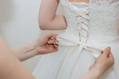 La mamá ayuda a la hija a llevar el vestido de boda Imágenes de archivo libres de regalías