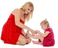 La mamá ayuda a la hija joven a llevar un deslizador Imagen de archivo libre de regalías