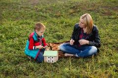 La mamá ayuda a mi hijo con la ayuda de un martillo a hacer un hous de madera Foto de archivo libre de regalías