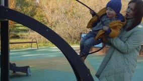 La mamá ayuda a poco hijo rubio a subir la diapositiva de madera usando cordaje almacen de video