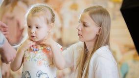 La mamá ayuda a su hija a llevar gotas coloreadas en la tienda para los niños imagenes de archivo